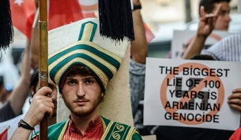 A Turkish nationalist protester wearing Ottoman clothes holds placard during a protest against Germany on June 2, 2016 in front of the Germany consulate in Istanbul after German parliament labelled the World War I massacre of Armenians by Ottoman forces as genocide.