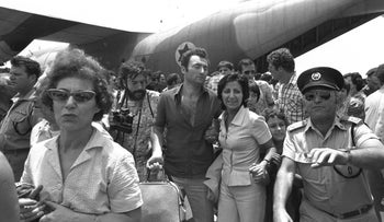 An Israeli police officer clears the way for the hostages returned to Israel after their ordeal in Entebbe, Uganda in 1976.