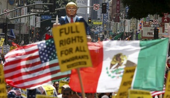 People march with an inflatable effigy of Donald Trump near American and Mexican flags during an immigrant rights May Day rally in Los Angeles, May 1, 2016.