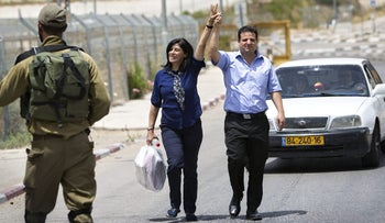 Palestinian lawmaker Khalida Jarrar walks with Joint List chief Ayman Odeh after her release from an Israeli prison near Tul Karm, June 3, 2016.