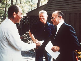 Egypt's President Anwar Sadat, left, shakes hands with Prime Minister Menachem Begin as U.S. president Jimmy Carter looks on in Camp David, September 1978.
