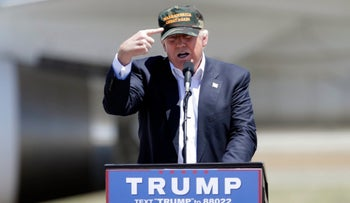 "Republican presidential candidate Donald Trump gestures to a his camouflaged ""Make America Great"" hat at a campaign rally at the Redding Municipal Airport Friday, June 3, 2016, in Redding, Calif."