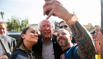 Democratic presidential candidate Bernie Sanders poses for a selfie with a couple in California on June 7, 2016.