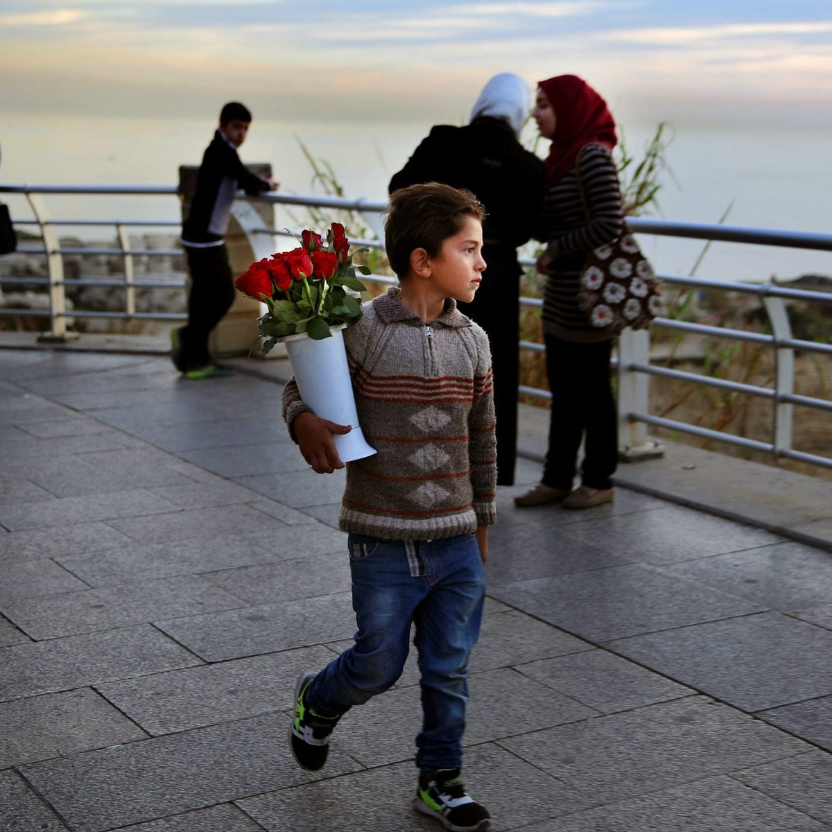 In this Thursday, Feb. 18, 2016 photo, Syrian refugee Ahmed Abrouch, 8, who fled with his family from Aleppo Syria, makes a living by selling flowers on the Mediterranean Sea waterfront promenade in Beirut, Lebanon. More than 1.1 million Syrians have sought refuge here since the start of the 2011 uprising, more than half of them children.