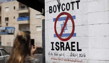 A tourist photographs a sign painted on a wall in the West Bank biblical town of Bethlehem on, calling to boycott Israeli products coming from Jewish settlements, June 5, 2015.