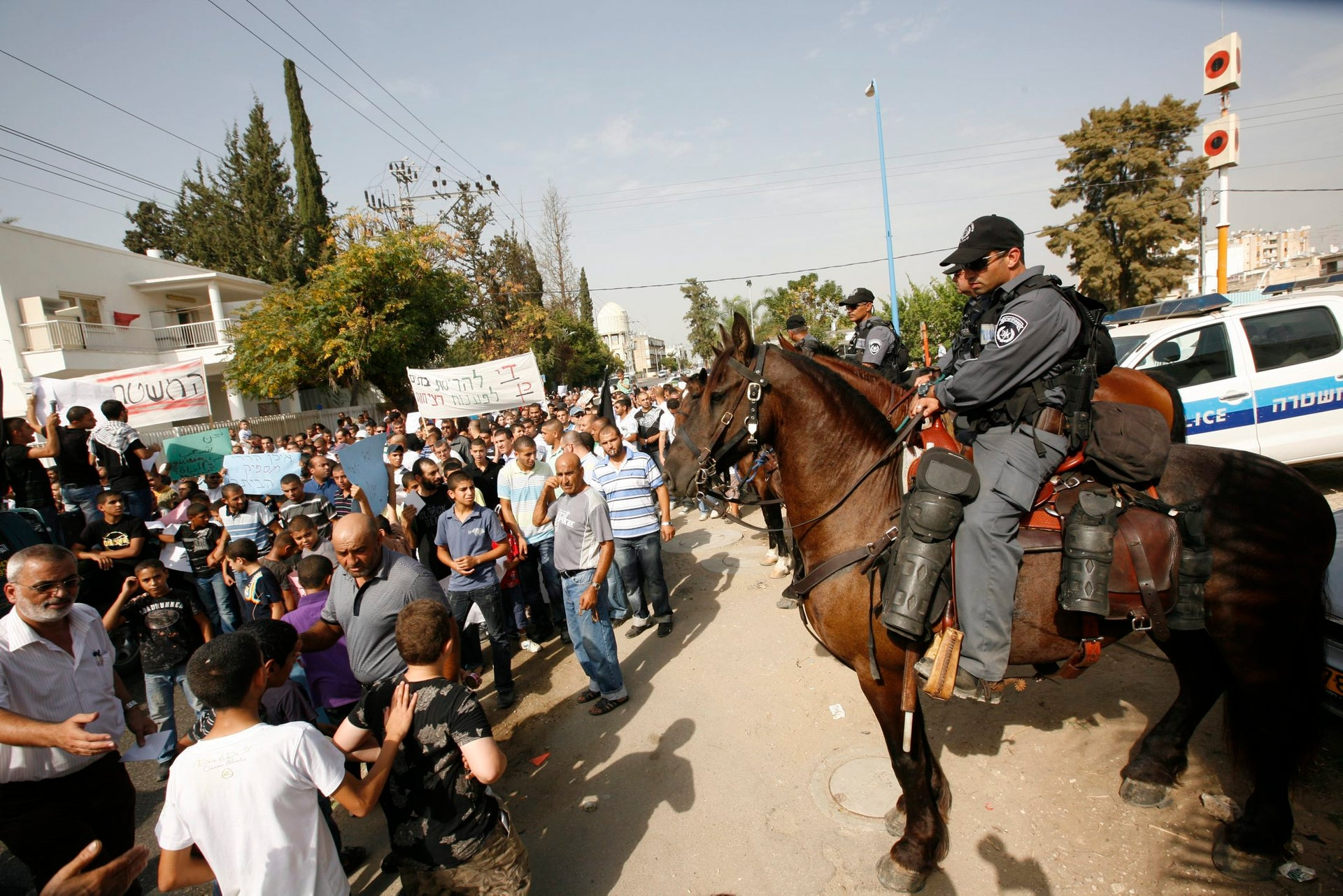 Lod residents protest the police's failure to curb gun violence, 2010. Demonstrators hold a sign saying 'The police is the prime suspect.'