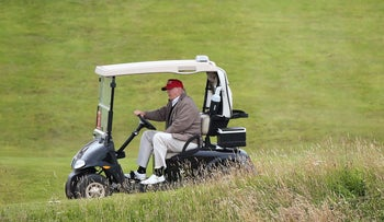 """Donald Trump drives his golf buggy during the Women's British Open golf championship in Turnberry, Scotland. Trump has called climate change a """"con job"""" and a """"hoax"""" but has applied for a permit to build a wall to keep out the rising seas threatening to swamp his luxury golf resort in Ireland."""