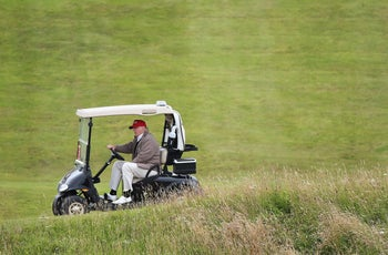 "Donald Trump drives his golf buggy during the Women's British Open golf championship in Turnberry, Scotland. Trump has called climate change a ""con job"" and a ""hoax"" but has applied for a permit to build a wall to keep out the rising seas threatening to swamp his luxury golf resort in Ireland."