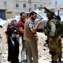 Israeli soldiers stop Palestinians at the entrance of Yatta, home of the Palestinians who shot and killed four Israelis in Tel Aviv, West Bank, June 9, 2016.