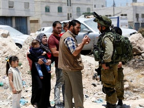 Israeli soldiers stop Palestinians at the entrance of Yatta near the West Bank city of Hebron June 9, 2016.