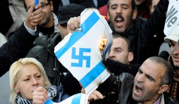 Protesters burn a swastika symbol during a pro-Palestinian protest against the Israeli military offensive in Gaza,  during a demonstration in Barcelona, Spain, Saturday, Jan. 10, 2009.