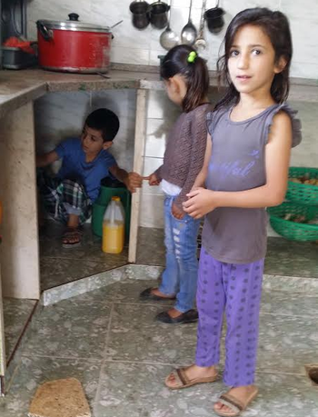 Khaled Mohammed Mahamra's six-year-old brother Taki hiding under the kitchen counter as his sisters look on with slightly more curiosity.