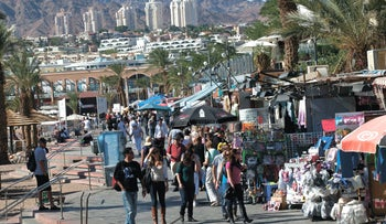 People stroll through a beach-side street in Israel's southern city of Eilat. The Eilat mountains and city landscape can bee seen in the background.