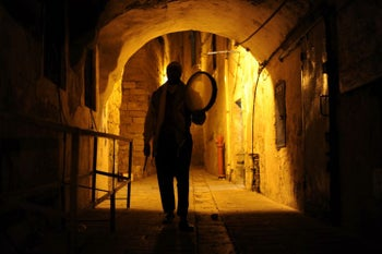 Drumming and singing, Michel Ayoub slowly walks across Acre's alleys.