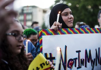 A Muslim woman holds a candle and a sign reading '#NotInMyName' to show that many in the Islamic faith support the LGBTQ community after the Orlando shooting, Seattle, U.S., June 12, 2016.