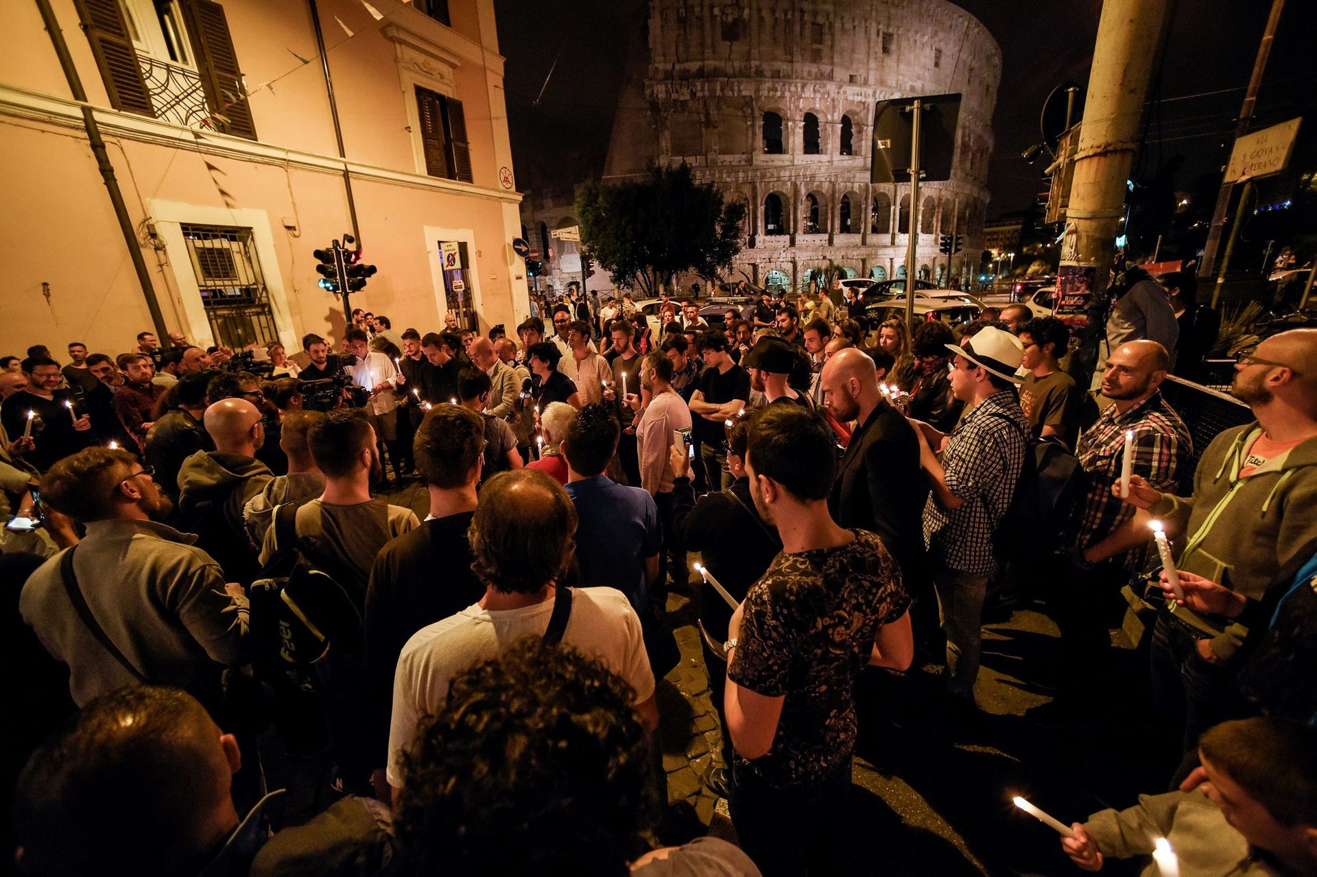 """Italian LGBT gay rights supporters hold candles as they take part in a ceremony in memory of the victims of the Orlando shooting, on June 12, 2016 in the """"Gay Street"""" gay- and lesbian-friendly neighborhood near Rome's Colosseum.  Fifty people were killed, in addition to the shooter, and 53 wounded in the worst mass shooting in US history, the mayor of Orlando Buddy Dyer said earlier on June 12. A fighter from the Islamic State group carried out the mass shooting, the IS-linked news agency Amaq said, quoting an unidentified source."""