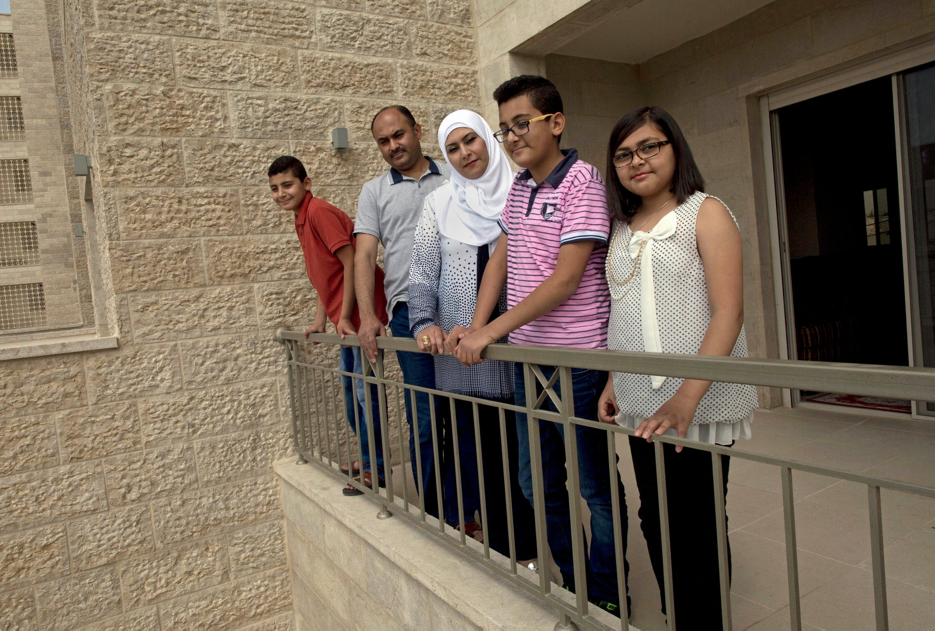 The al Khateeb family pose for a photo on the terrace of their newly delivered apartment in West Bank city of Rawabi, north of Ramallah, June 4, 2016.