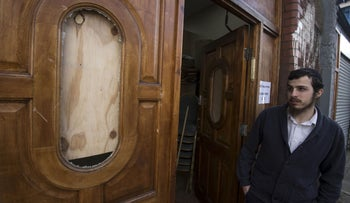 A Jewish man surveying a damaged door outside the Ahavas Torah synagogue in the Stamford Hill area of north London on March 22, 2015.