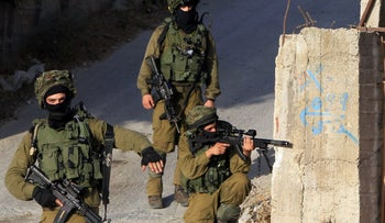 Soldiers hold a position in a street, east of the West Bank city of Nablus, on October 3, 2015, as they search for the suspected Palestinian killers of a Jewish settler couple.