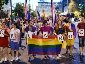 People hold a rainbow flag during a rally to pay tribute for the victims of the Orlando shooting, Athens, Greece, June 14, 2016.