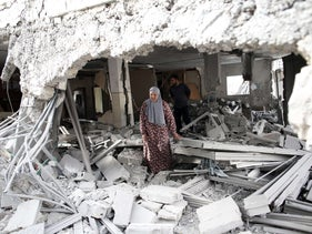 A Palestinian woman walks amid the rubble of a house after Israeli security forces demolished the homes of two convicted Palestinian terrorists in Jabal Mukkaber in East Jerusalem, October 6, 2015.