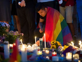 A man wrapped in a Rainbow Flag lights a candle during a vigil in Washington in memory of the victims of the Orlando mass shooting, hosted by the Muslim American Women's Policy Forum, on June 13, 2016.