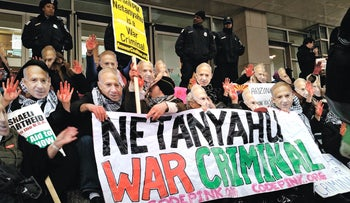 """Anti-Israel demonstrators wearing masks bearing the likeness of Israeli Prime Minister Benjamin Netanyahu and holding up """"bloody"""" hands protest March 1, 2015 outside the Washington Convention Center, where Netanyahu was due to speak."""