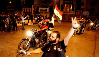 In this Saturday, June 18, 2016 photo, People take part in a celebration after Iraqi special forces entered the center of Fallujah city early Friday after fighting Islamic State militants, at Tahrir Square in Baghdad, Iraq.