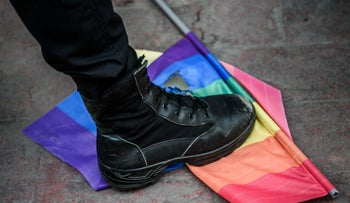 A Turkish anti-riot police officer steps on a rainbow flag during a rally staged by the LGBT community on Istiklal avenue in Istanbul on June 19, 2016.