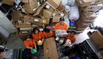 Young people from Ark of Hope amid a mountain of paper, cardboard and other items ready for recycling.