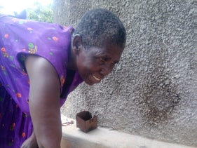 A woman drawing water from a rainwater harvesting tank.