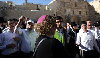 Ultra Orthodox Jewish men shout as they surround a member of the liberal Reform movement during an egalitarian prayer service at the Western Wall, Jerusalem, Israel, June 16, 2016.