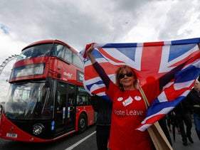 A campaigner wearing a Vote Leave t-shirt and holding a British Union Flag stands on a Westminster Bridge near the Houses of Parliament, London, U.K., June 15, 2016.