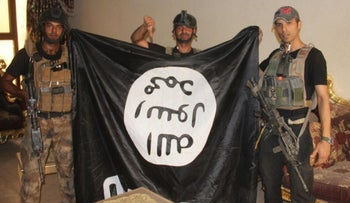 Iraqi soldiers pose with an ISIS flag after forces re-took Fallujah from the militant group, Fallujah, Iraq, June 19, 2016.