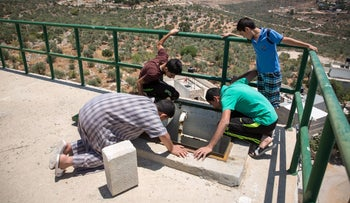 Residents of Qarawat Bani Hassan in the West Bank check the village's water tank. The settlement of Kiryat Netafim is in the background, June 20, 2016.