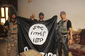 Soldiers pose with an ISIS flag in Fallujah, Iraq after forces re-took the city center after two years of ISIS control, June 19, 2016.