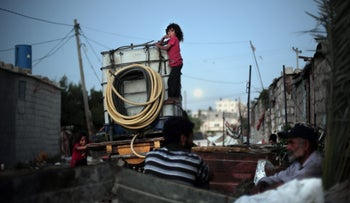 Palestinian children climb on a portable tank used to distribute water near Khan Younis refugee camp, southern Gaza Strip, June 20, 2016.