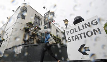 A woman carries an umbrella past a pub being used as a polling station for the Referendum on the European Union in London on June 23, 2016.