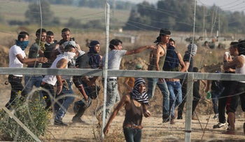 Palestinian protesters near border fence between Israel and the Gaza Strip during clashes with Israeli security forces on October 13, 2015.