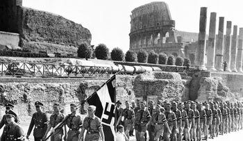 The Coliseum forms the background as a contingent of German Hitler Youth, carrying a Nazi banner, march through ancient Rome, Sept. 28, 1936.