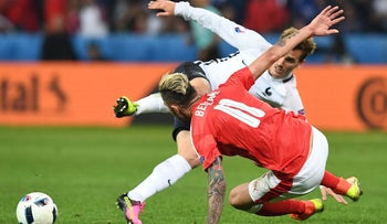 France's forward Antoine Griezmann (back) is fouled by Switzerland's midfielder Valon Behrami during the Euro 2016 group A football match between Switzerland and France, June 19, 2016.