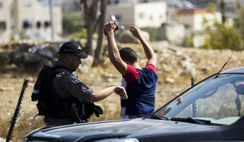 A Border Policeman performs a security check on a Palestinian at a checkpoint in the Jabal Mukkaber section of East Jerusalem, October 14, 2015.