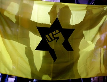 An Israeli right wing activist holds up the flag of the outlawed Kach movement as he rallies against an Israeli left-wing demonstration in Jerusalem, October 17, 2015.