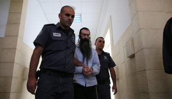 Yishai Schissel is led through the Jerusalem District Court on Sunday, June 26, 2016.