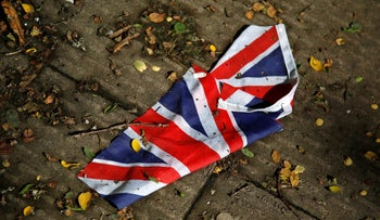 A British flag that was washed away by heavy rains the day before lies on the street in London, June 24, 2016 after Britain voted to leave the European Union.