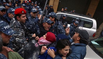 Lebanese anti-government protesters clash with policemen outside the Environment Ministry in support of activists who were detained after staging a sit-in inside, in downtown Beirut, Lebanon, Thursday, Jan. 14, 2016.