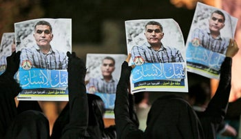 Bahraini anti-government protesters hold up images of Rajab after he was detained by authorities May 14, 2015.