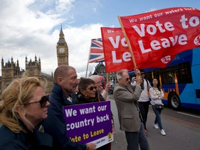 'Leave' supporters hold banners and flags as they stand on Westminster Bridge during a campaign stunt in favor of Brexit, London, U.K., June 15, 2016.