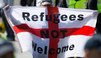 "A protestor holds up a flag that reads ""Refugees Not Welcome"" during a demonstration by far right protesters in the town of Dover in south east England, on May 28, 2016."