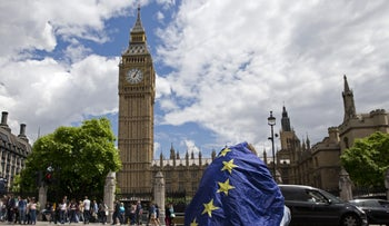 A demonstrator draped in an EU flag sits on floor during a protest against the outcome of the UK's June 23 referendum on the European Union (EU), in central London on June 25, 2016.